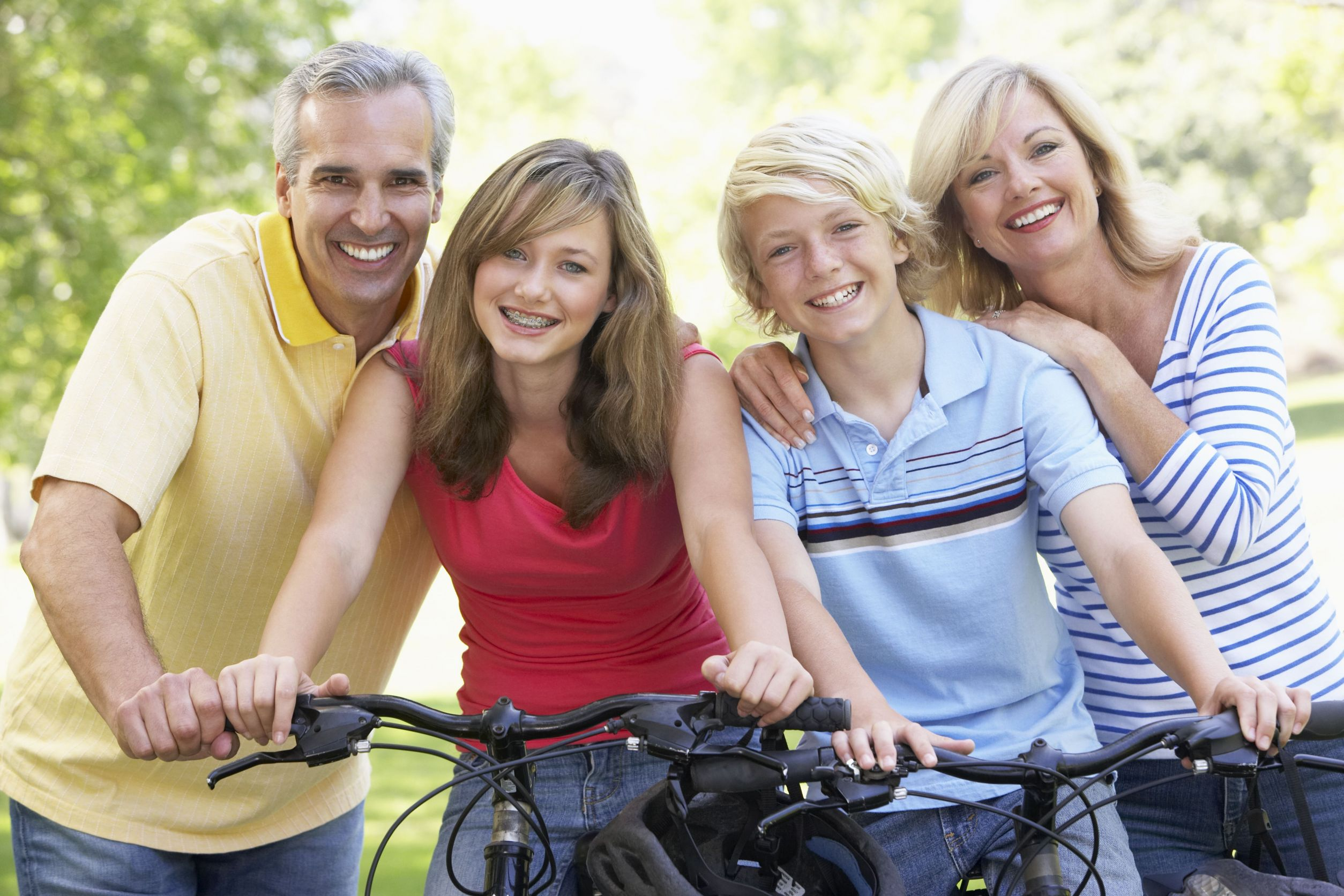 Family riding bikes and smiling